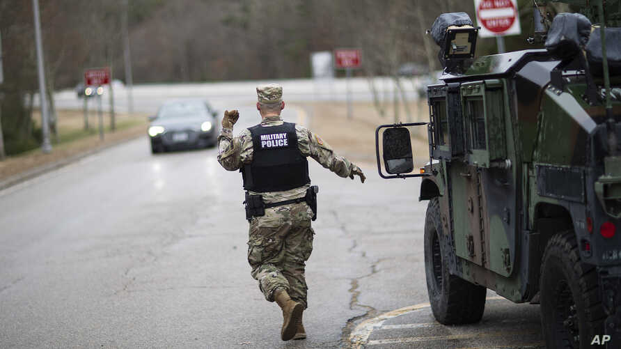 A member of the Rhode Island National Guard Military Police directs a motorist with New York license plates at a checkpoint on…