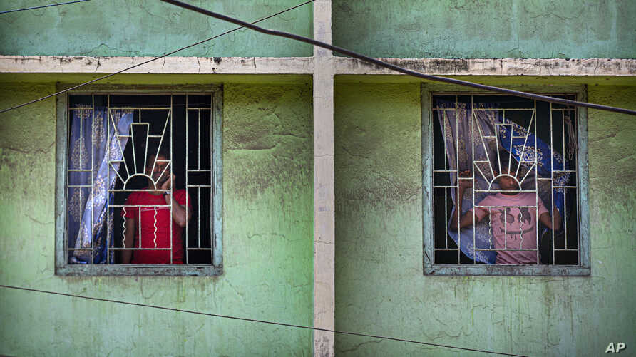 Indians look through the windows of a building during a lockdown to control coronavirus spread, in Gauhati, India, Wednesday,…