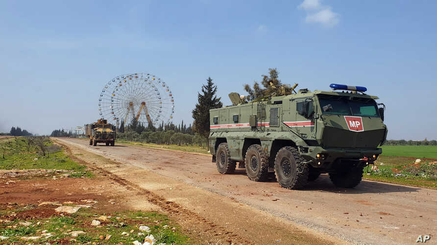 In this photo provided by the Turkish Defense Ministry, Turkish and Russian troops patrol on the M4 highway, which runs east…