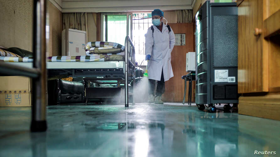 A doctor disinfects a room for medical staff with sanitizing equipment at a community health service center, which has an…