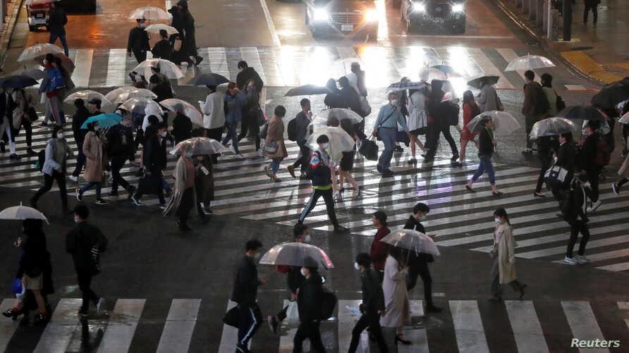 Pedestrians walk past a scramble crossing during the first weekend after Tokyo Governor Yuriko Koike (not in picture) urged the…