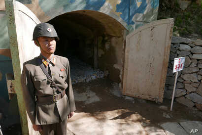 FILE - In this May 24, 2018 photo, a guard stands at the entrance of the north tunnel at North Korea's nuclear test site, which was blown up soon after this photo was made, in a display of dismantling the test site, at Punggye-ri, North Hamgyong Provin...