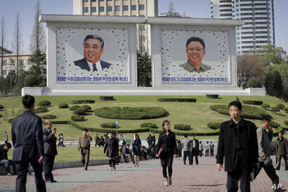 People walk beneath portraits of late leaders, Kim Il Sung, left, and Kim Jong Il, in Pyongyang, North Korea, April 18, 2017.
