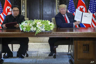 FILE - U.S. President Donald Trump holds up the document that he and North Korea leader Kim Jong Un had signed at the Capella resort on Sentosa Island, June 12, 2018, in Singapore.