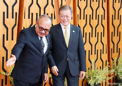 South Korea's President Moon Jae-in is shown the way by Papua New Guinea's Prime Minister Peter O'Neill as he arrives for the APEC Summit, Port Moresby, Papua New Guinea, Nov. 17, 2018. Moon is expected to discuss North Korea sanctions with Chinese Pre...