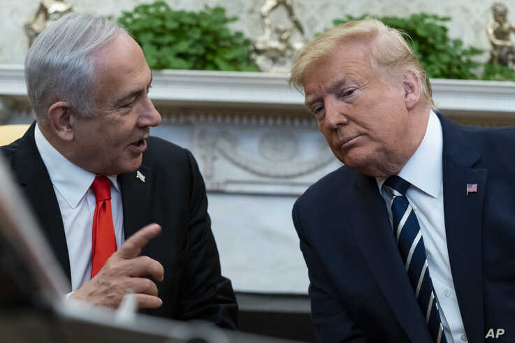President Donald Trump listens to Israeli Prime Minister Benjamin Netanyahu during a meeting in the Oval Office of the White…