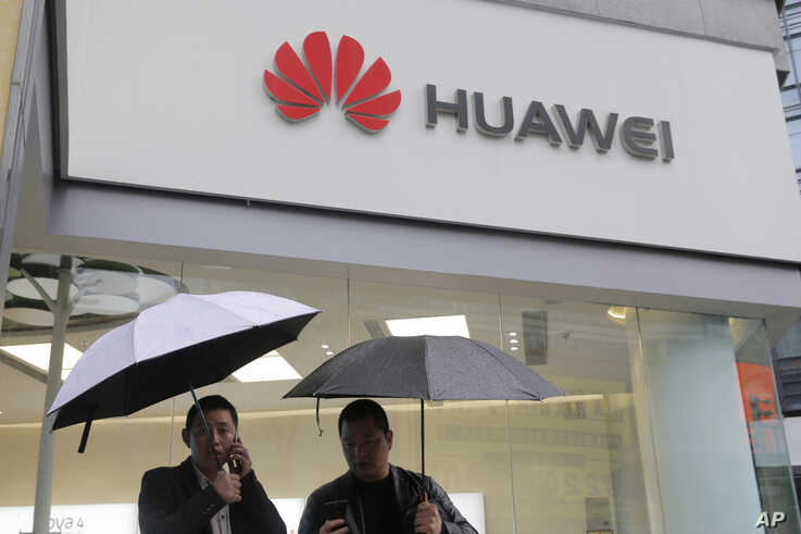 FILE - In this Thursday, March 7, 2019 file photo, two men use their mobile phones outside a Huawei retail shop in Shenzhen,…