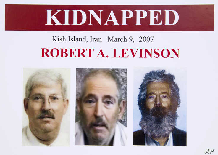 FILE- In this March 6, 2012 file photo, an FBI poster showing a composite image of former FBI agent Robert Levinson, right, of…